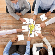 Ihmiset pöydän ympärillä hahmottamassa yhteistä ideaa, jota kuvaa palapelin kokoaminen.