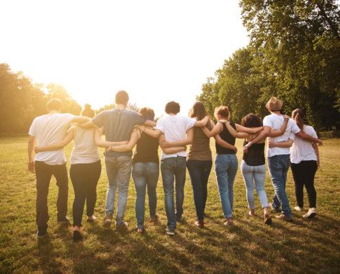 kymmenen ihmistä kävelee rinnakkain kädet toistensa hartioilla