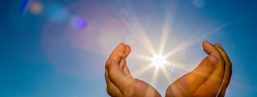 kädet, joiden taustalla taivas, ja aurinko näyttää paistavan käsien välistä.