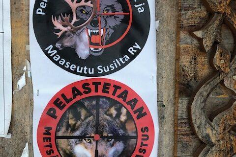 Kaksi tarraa seinässä: toinen vaatii maaseudun pelastamista susislta ja toinen metsästysharrastuksen pelastamista.
