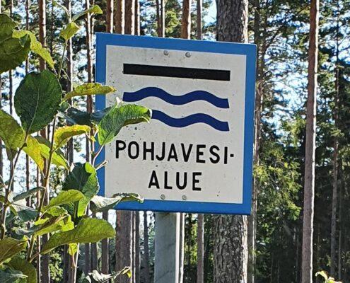 kyltti, jossa pohjavesialueen merkki, taustalla metsää.
